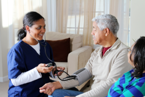 caregiver monitoring the patients blood pressure