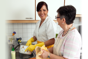 caregiver helping her patient wash the dishes